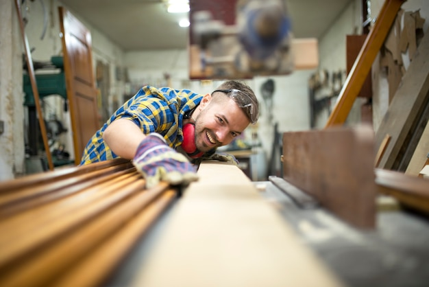 Portrait of experienced carpenter worker cutting wood plank on the machine in his woodworking workshop