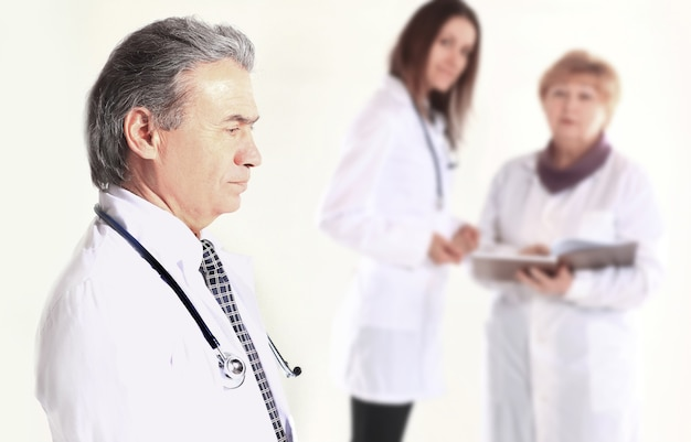 Portrait of an experienced doctor in the background of the employees of the medical center.