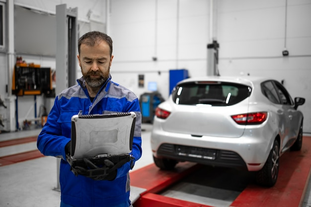Portrait of an experienced middle aged bearded car mechanic holding laptop computer diagnostic tool in vehicle workshop for service and maintenance.