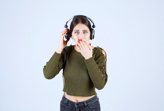 Ritratto di giovane ragazza espressiva che ascolta musica e si copre la bocca.