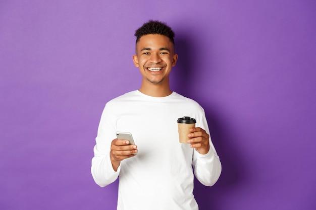 Портрет выразительный молодой человек, держащий чашку кофе и мобильный