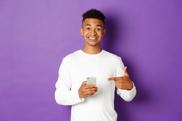 Portrait expressive young man holding mobile