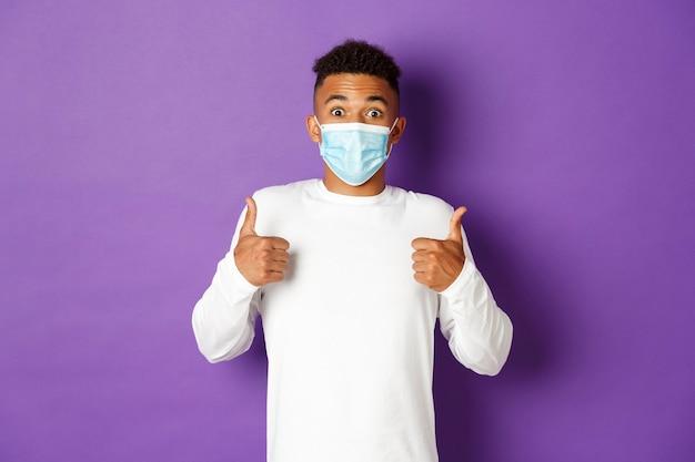 Портрет выразительного молодого человека в медицинской маске