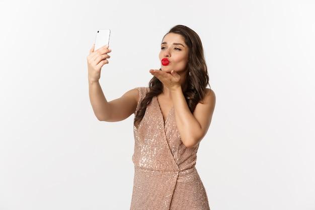 Portrait expressive young woman in elegant dress taking selfie
