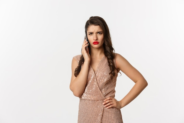 Portrait expressive young woman in elegant dress using phone