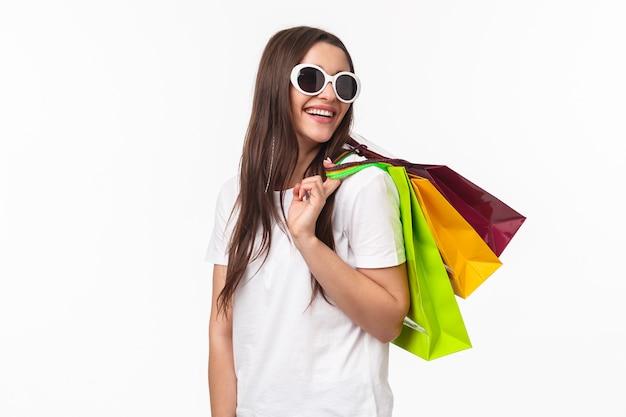 Портрет выразительной молодой женщины, держащей хозяйственные сумки