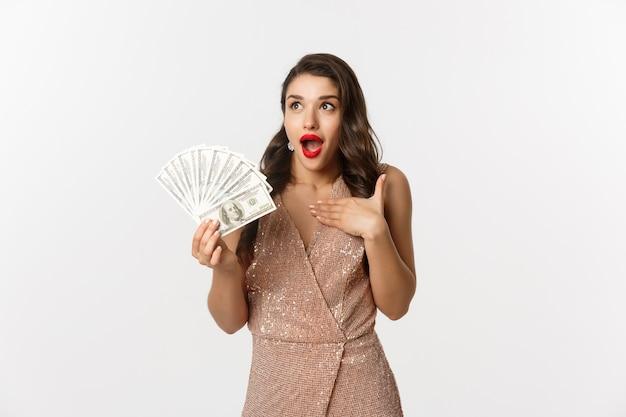 ドル紙幣を保持しているエレガントなドレスの肖像画の表現力豊かな若い女性
