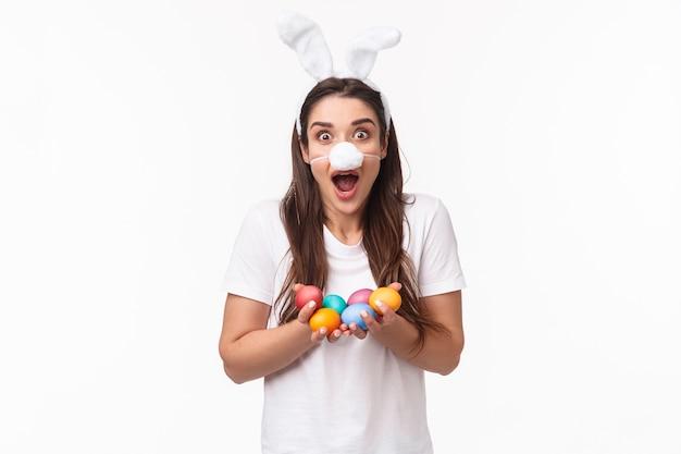 Ritratto espressivo giovane donna indossa orecchie di coniglio e naso, tenendo in mano le uova colorate