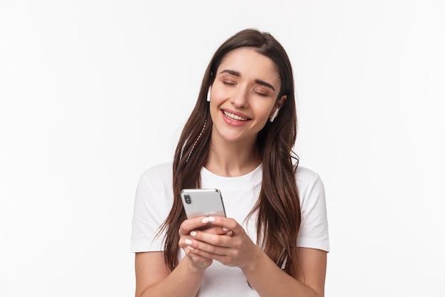 Ritratto espressiva giovane donna con airpods e mobile