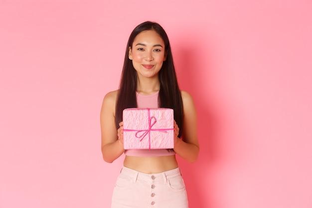 Портрет выразительной молодой женщины с подарочной коробкой