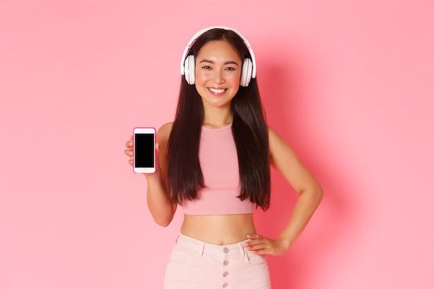 Портрет выразительной молодой женщины с наушниками, слушающей музыку