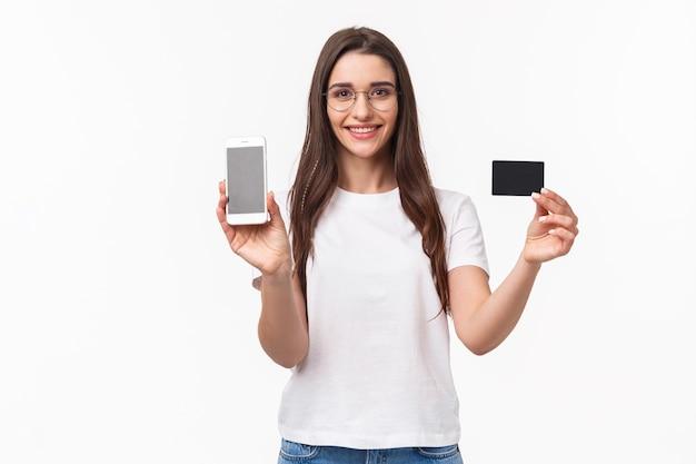 Портрет выразительной молодой женщины с мобильным телефоном и кредитной картой