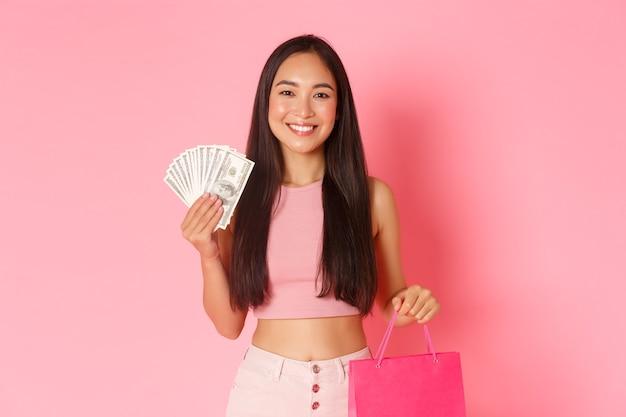 ショッピングバッグとお金を持つ肖像画表現力豊かな若い女性