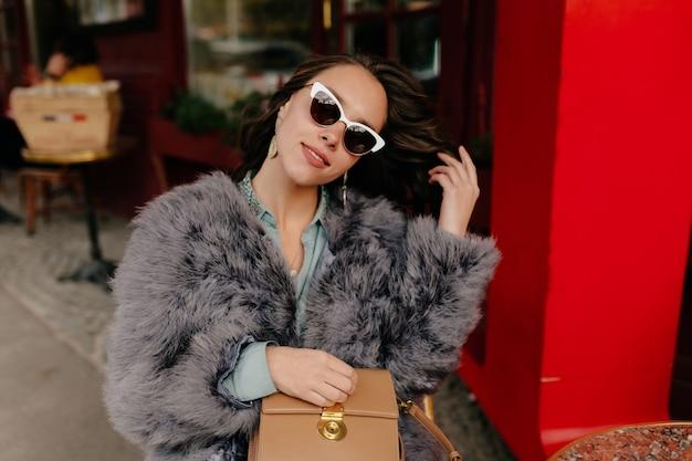 Ritratto di favolosa giovane donna con i capelli scuri, vestito di pelliccia e occhiali da sole.