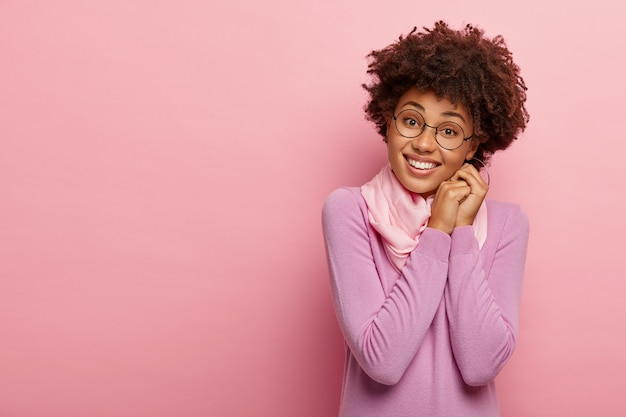 Ritratto di donna graziosa favolosa tiene i palmi premuti insieme vicino al viso, lieta di sentire qualcosa di piacevole, indossa occhiali trasparenti rotondi, modelli in studio, indossa un maglione casual