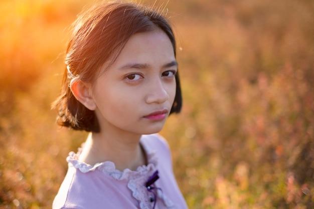 茶色の野原の草でカメラを見ている肖像画の顔の若いアジアの女の子。