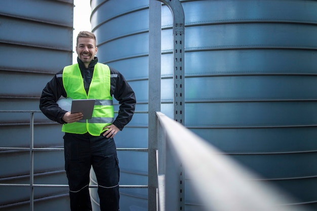 Portrait of factory engineer worker standing on metal platform between industrial storage tanks and looking to the camera