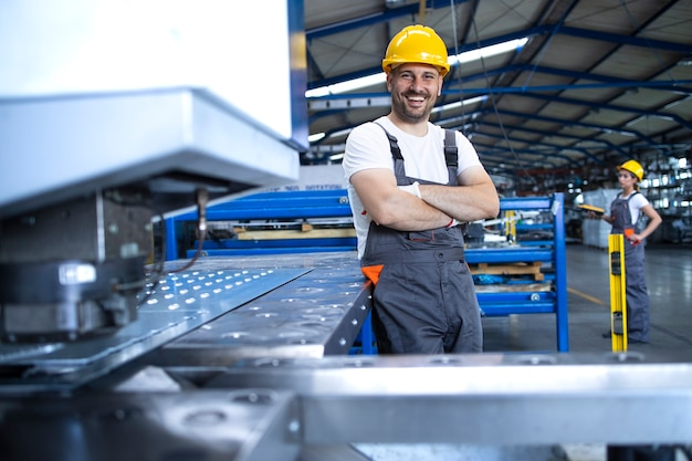 Ritratto di operaio di fabbrica in uniforme protettiva e hardhat in piedi dalla macchina industriale alla linea di produzione