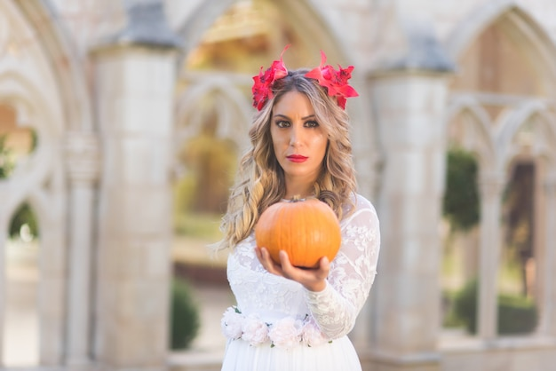 Portrait of a fairy tale queen holding a pumpkin