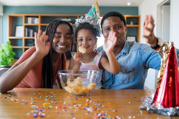 Ritratto di una famiglia che festeggia il compleanno online durante una videochiamata restando a casa