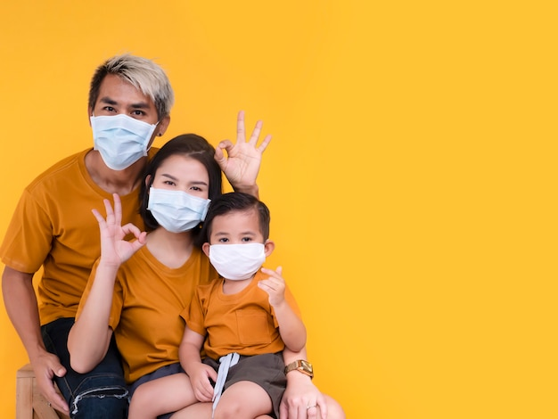 Portrait of family group showing ok sign and wearing protective mask trying to protect from virus