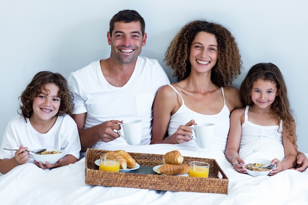 Portrait of family having breakfast in bed