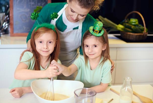 Portrait of family mixing dough