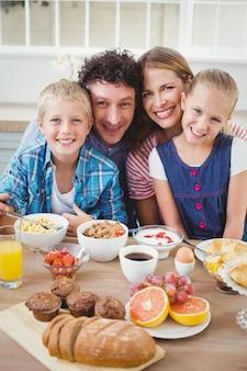 Portrait of family smiling while having breakfast