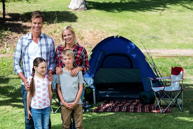 Portrait of a family standing outside the tent