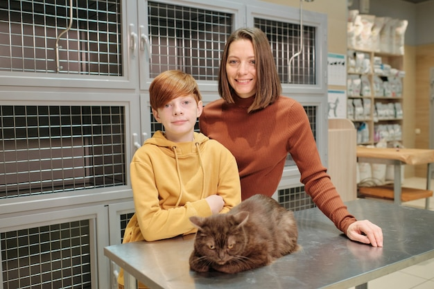 Portrait of family of two smiling at camera while standing at vet clinic with their cat on the table