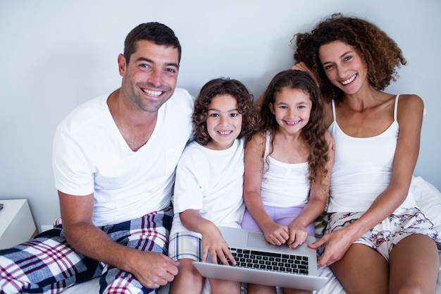 Portrait of family using laptop together on bed