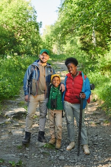 Portrait of family with their son smiling at camera while go hiking in the forest