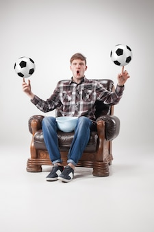 Portrait of fan with football balls, holding dish on gray