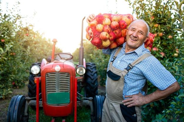 Ritratto del lavoratore agricolo che tiene il sacco pieno di frutta mela