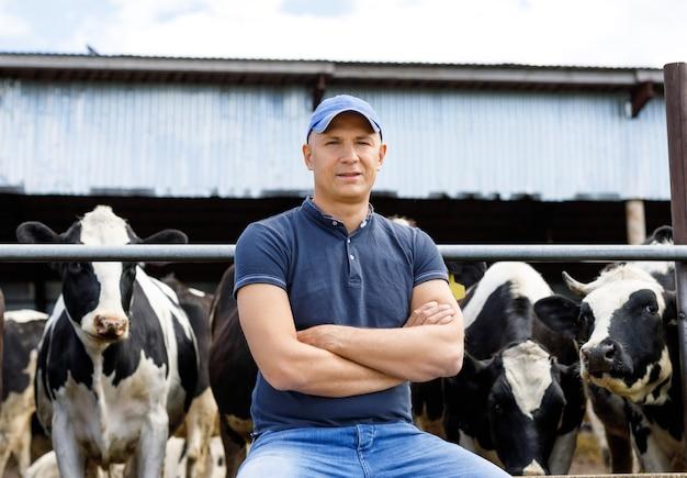 Portrait of a farmer among cows on a farm
