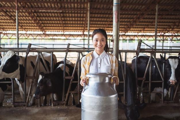 農家のアジアの女性の肖像画は彼の農場で牛乳のコンテナーを保持しています。