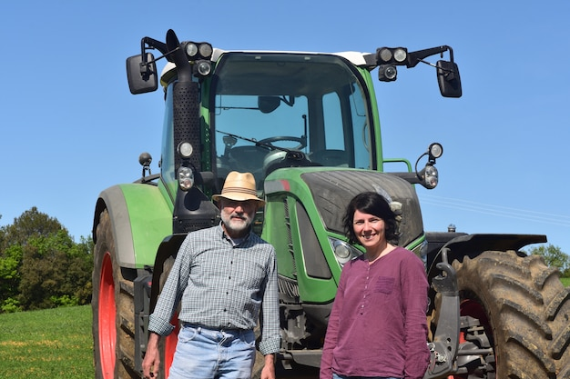 Portrait of a farmer couple and tractor on the field