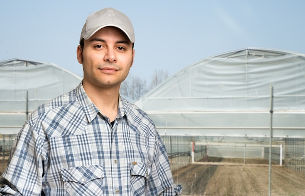 Portrait of a farmer in front of a greenhouse