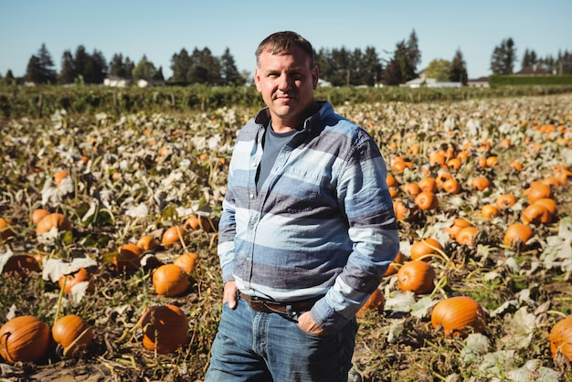 Portrait of farmer standing in pumpkin field