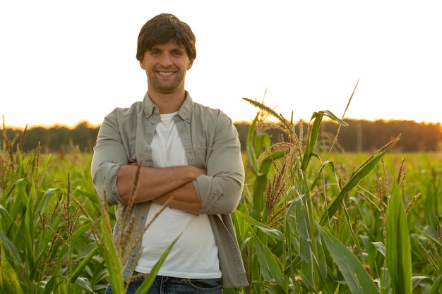 Portrait of a farmer with his arms crossed standing in a corn field looking at the camera