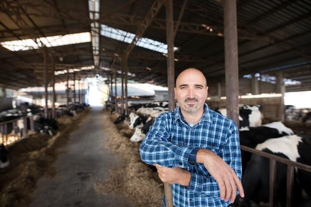 Ritratto di lavoratore agricoltore in piedi presso l'allevamento di bestiame