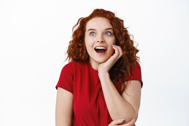 Portrait of fascinated young woman with red curly hiar, gasping amazed, staring excited at left side with copy space  standing over white wall