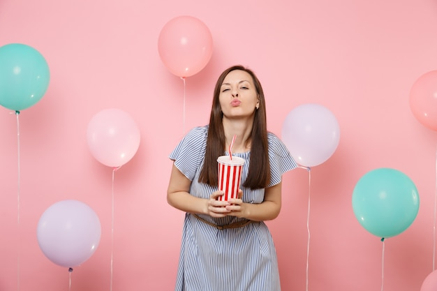 Portrait of fascinating happy young woman wearing blue dress blowing lips kiss holding plastic cup of cola or soda on pastel pink background with colorful air balloons. birthday holiday party concept.