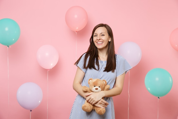 Portrait of fascinating joyful young woman in blue dress holding and hugging teddy bear plush toy on pink background with colorful air balloons. birthday holiday party people sincere emotions concept.
