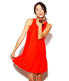Portrait of fashion cute young woman model in a red dress on a white wall giving a kiss