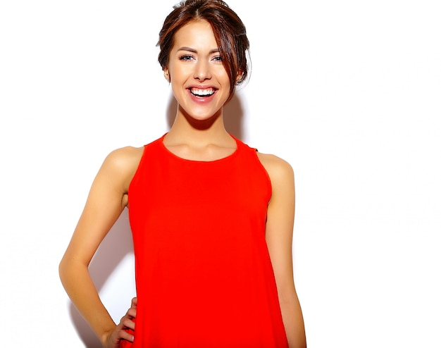 Portrait of fashion  cute young woman model in a red dress on a white wall