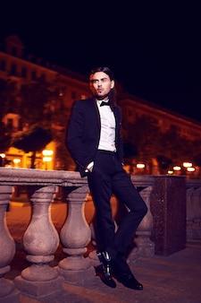 Ritratto di moda elegante giovane dai capelli lunghi. modello maschio attraente e bello in abito nero con i baffi in strada di notte