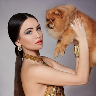 Portrait of a fashion model with a small dog in his hands