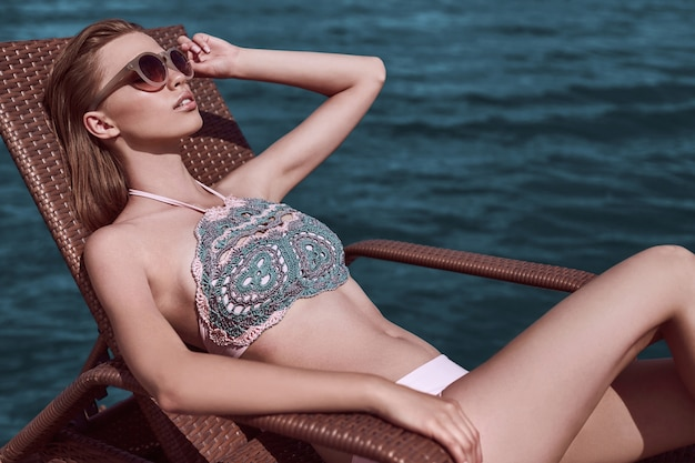 Portrait of fashion, seductive girl in knitted swimsuit