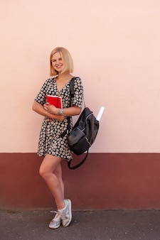 Portrait of fashion smiling student girl with black backpack and holding red dairy